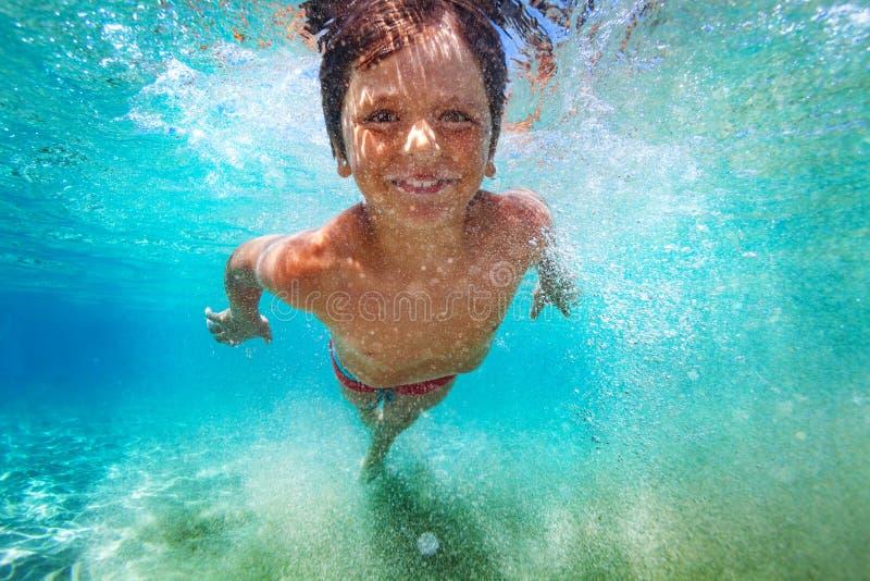 学会愉快的男孩游泳在水面下 库存照片