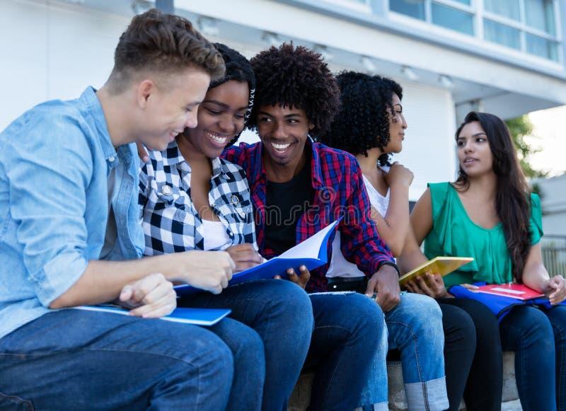 学会户外在校园里的大小组国际学生 免版税图库摄影