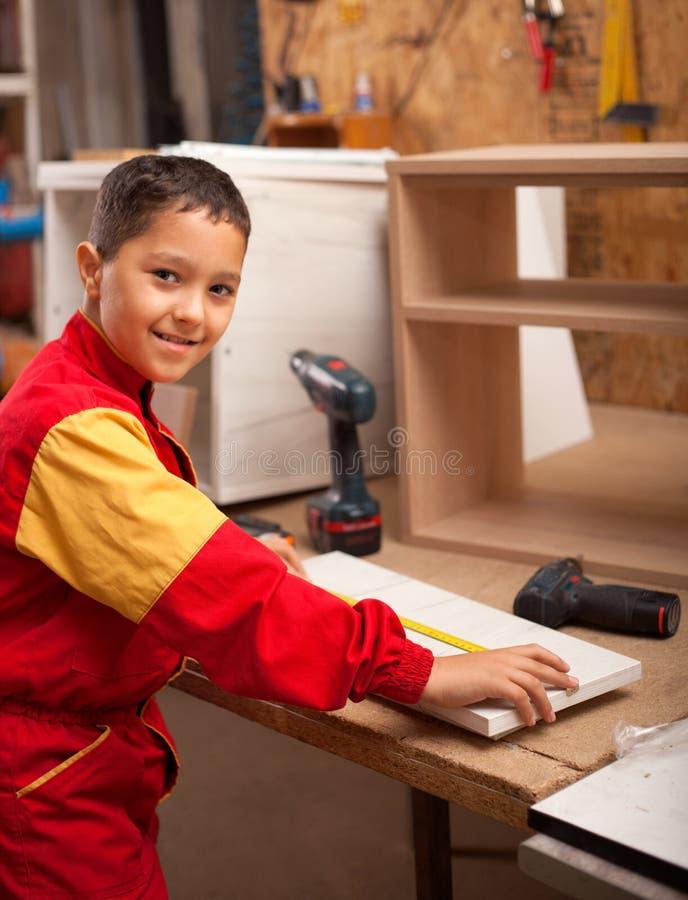 学会木头雕刻的男孩 工作在车间的年轻木匠 库存图片