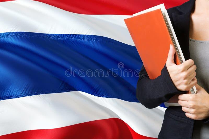 学会泰语概念 与泰国旗子的年轻女人身分在背景中 拿着书,橙色空白的老师 免版税图库摄影