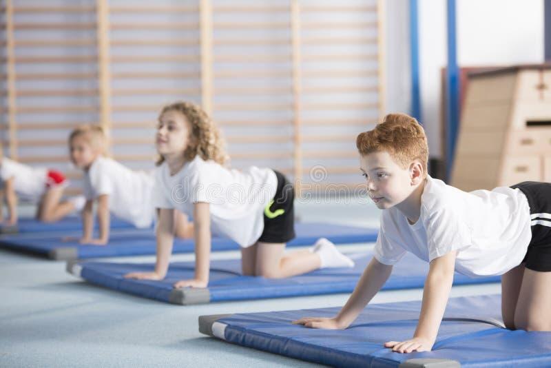 学会瑜伽姿势的年轻男孩 免版税库存照片