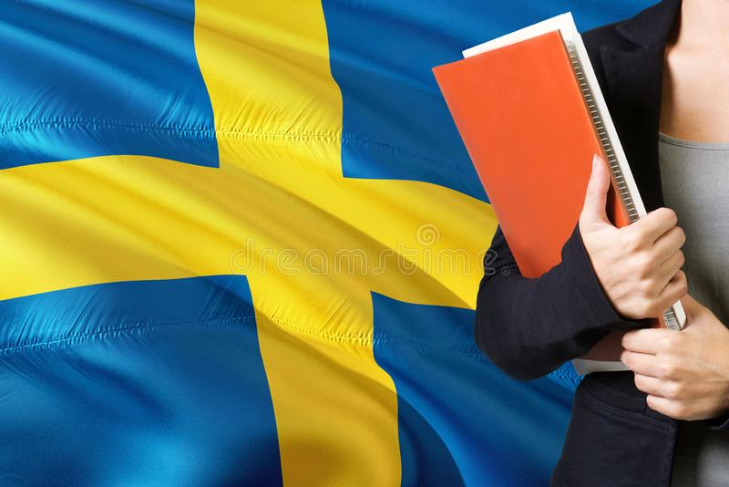 学会瑞典语言概念 与瑞典旗子的年轻女人身分在背景中 拿着书,桔子的老师 库存图片