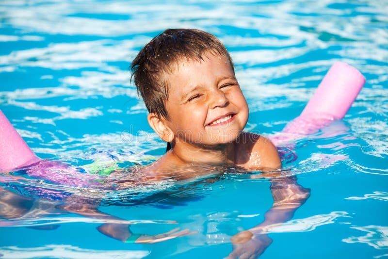 学会男孩的特写镜头游泳用水池面条 免版税库存图片