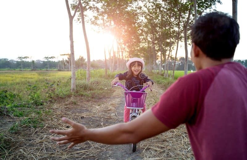 学会的女儿骑有爸爸的自行车 免版税库存照片