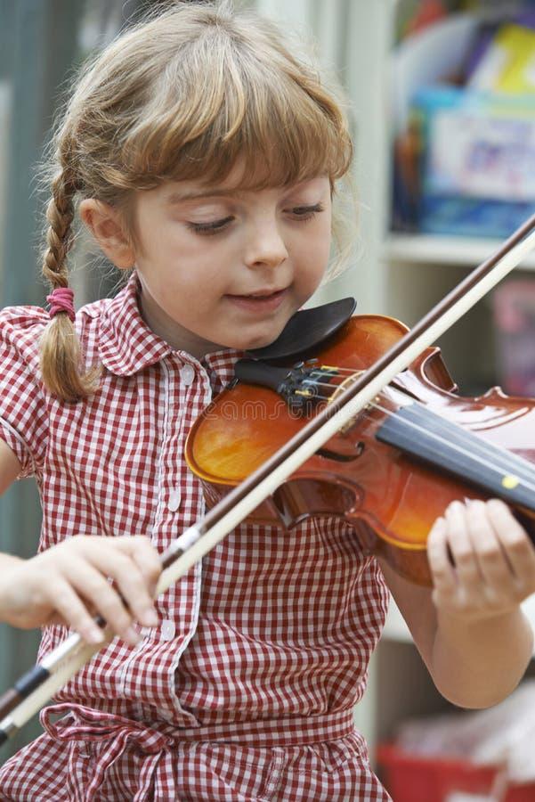 学会的女孩在学校弹小提琴 免版税库存图片