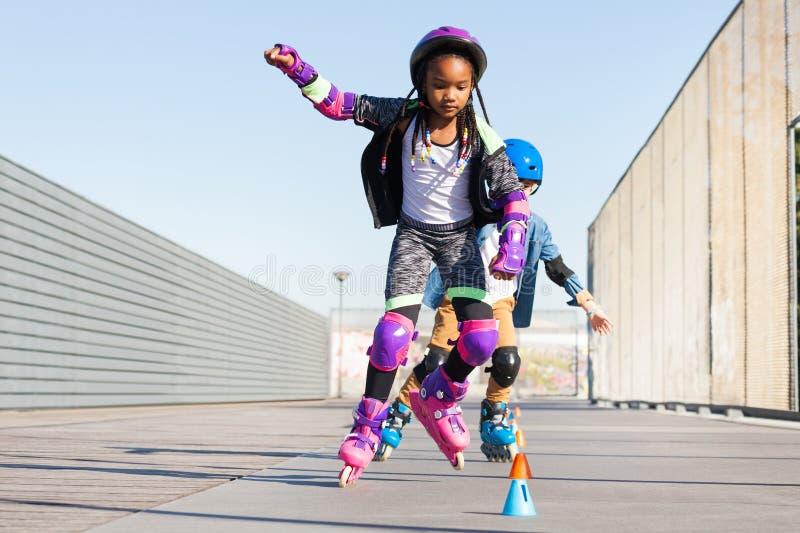 学会的女孩进行障碍滑雪与轴向冰鞋的冰鞋 免版税库存图片