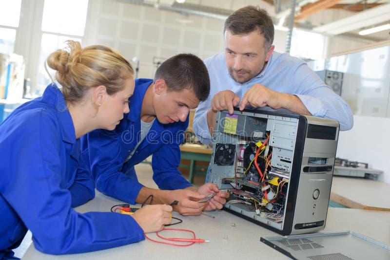 学会的学生修理计算机 免版税库存照片
