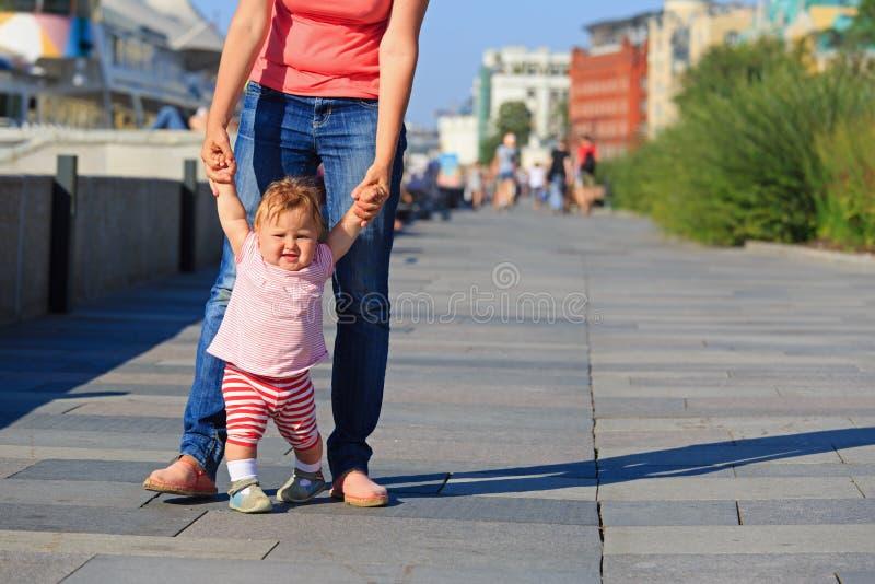 学会的母亲和的婴孩在城市公园走 免版税库存照片