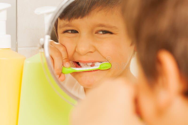 学会的男孩看在玻璃和刷牙 免版税图库摄影