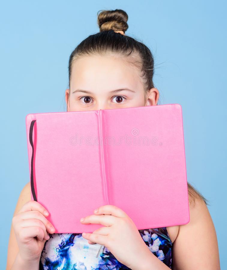 学会看书 秘密故事 写的作业簿 做的笔记学校日志 有笔记本的小女孩 免版税库存照片