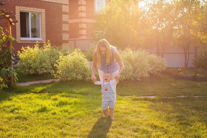 学会第一步小可爱的小孩男孩,愉快和逗人喜爱的婴孩走与母亲,母亲` s天概念 免版税库存照片