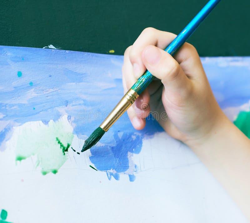 学会绘画图画艺术概念的小男孩 孩子的手拿着一把刷子,并且在白皮书的油漆绿化 免版税库存图片