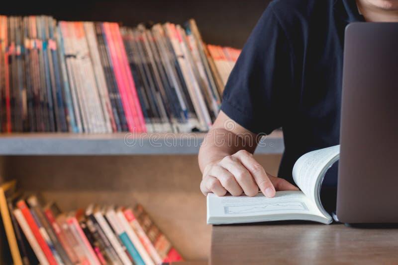 学会股票交易的年轻商人 坐在图书馆看书,使用做研究的膝上型计算机的学习参考书的人 免版税库存照片