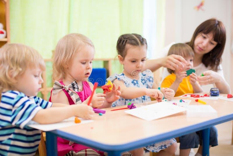 学会艺术和工艺的孩子在有老师的幼儿园 免版税图库摄影
