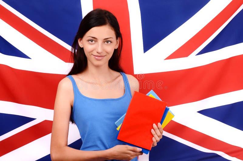学会英语。拿着书,红色空白的书套的美丽的学生。 免版税图库摄影