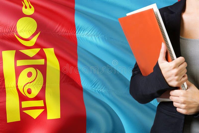 学会蒙古语言概念 与蒙古旗子的年轻女人身分在背景中 拿着书,桔子的老师 免版税库存照片