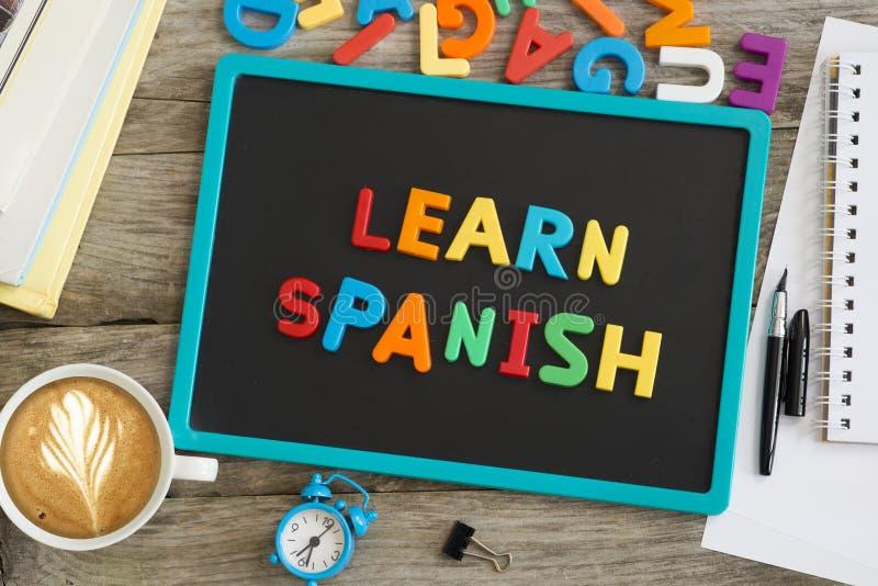 学会西班牙忠告写与五颜六色的塑料信件在黑板 图库摄影