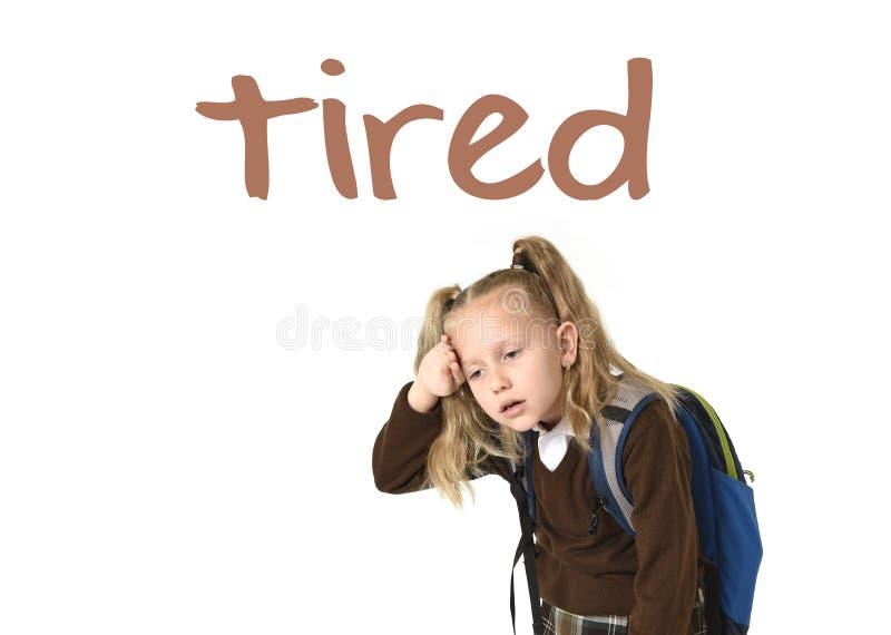 学会词汇量与词的英语学校卡片疲倦了和甜美丽的矮小的女小学生 免版税库存照片