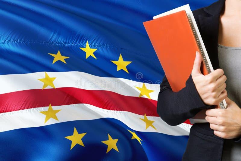 学会语言概念 与佛得角旗子的年轻女人身分在背景中 拿着书,橙色空白的老师 免版税库存照片