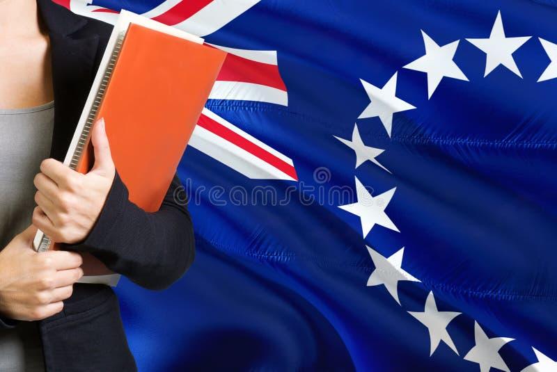 学会语言概念 与库克群岛旗子的年轻女人身分在背景中 拿着书,橙色空白的老师 库存图片