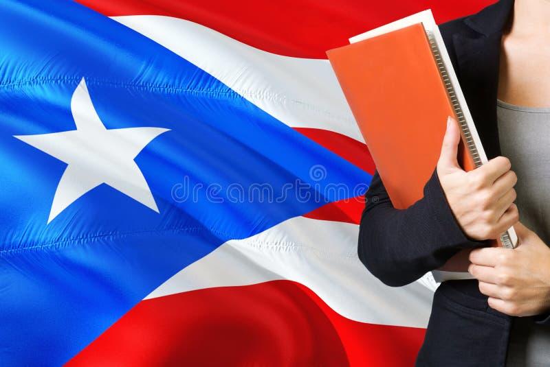 学会语言概念 与波多黎各旗子的年轻女人身分在背景中 拿着书,橙色空白的老师 库存照片