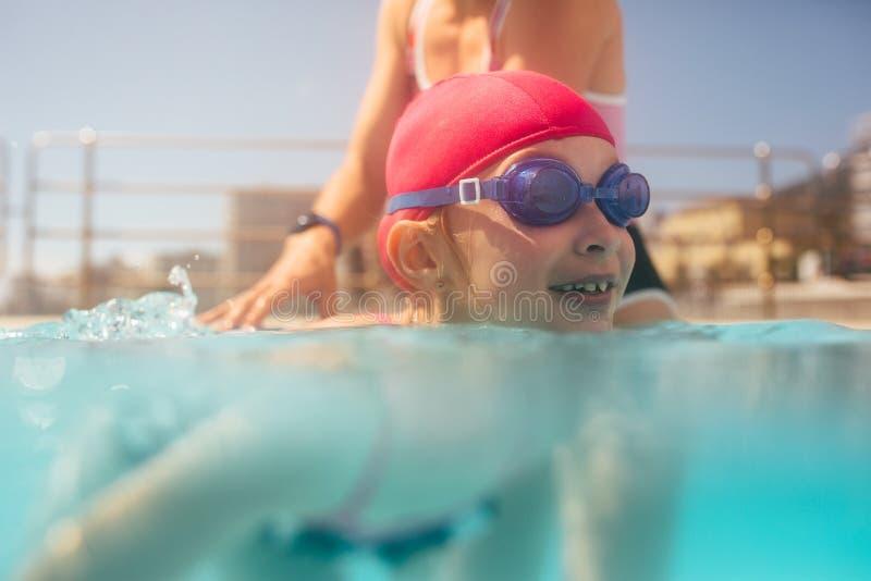 学会逗人喜爱的女孩游泳与教练 免版税库存图片