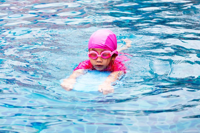 学会逗人喜爱的小女孩游泳与教练在游泳池 免版税库存照片