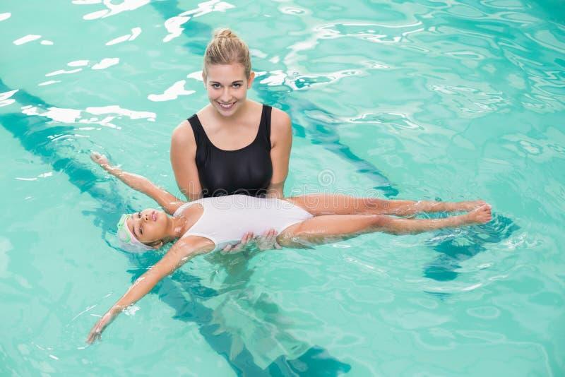 学会逗人喜爱的小女孩游泳与教练 免版税库存照片