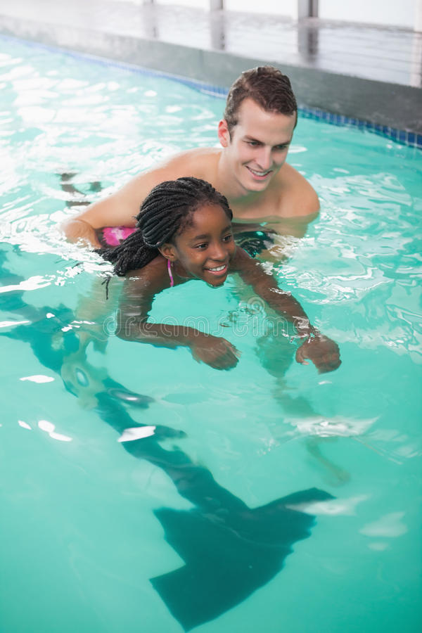学会逗人喜爱的小女孩游泳与教练 免版税库存图片
