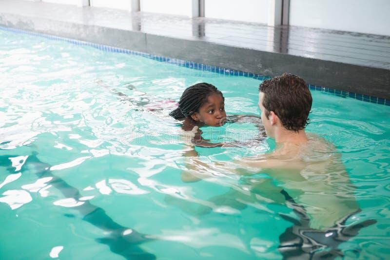 学会逗人喜爱的小女孩游泳与教练 库存照片