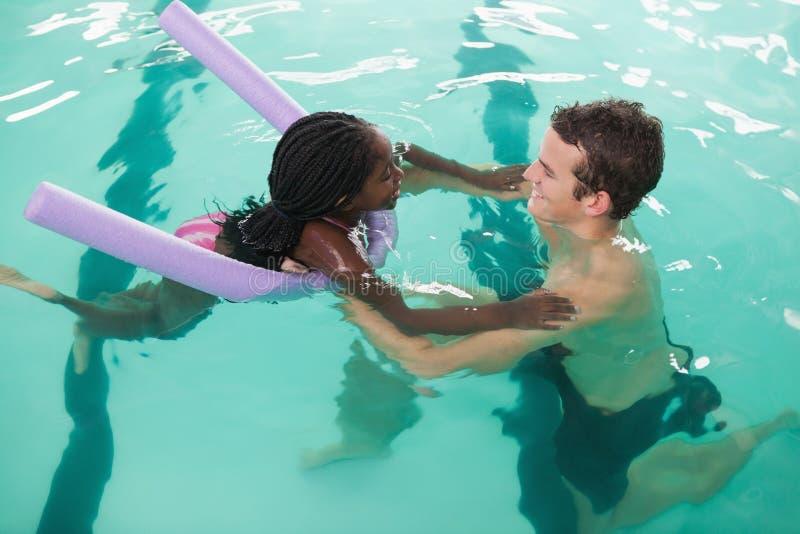 学会逗人喜爱的小女孩游泳与教练 库存图片