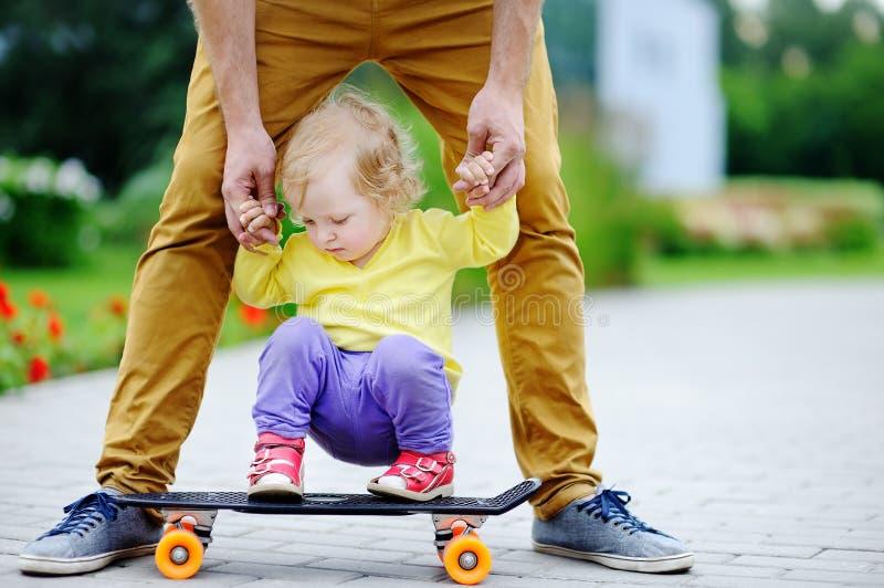 学会逗人喜爱的小孩的女孩踩滑板与她的父亲 库存照片