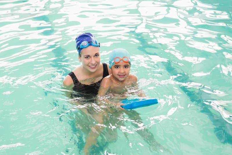 学会逗人喜爱的小男孩游泳与教练 免版税库存图片