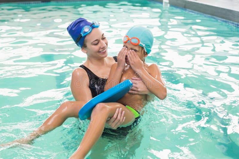 学会逗人喜爱的小男孩游泳与教练 图库摄影
