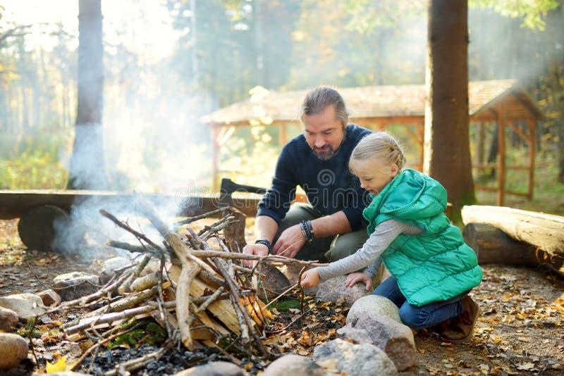 学会逗人喜爱的少女开始篝火 教她的女儿的父亲做火 孩子获得乐趣在阵营火 ?? 图库摄影