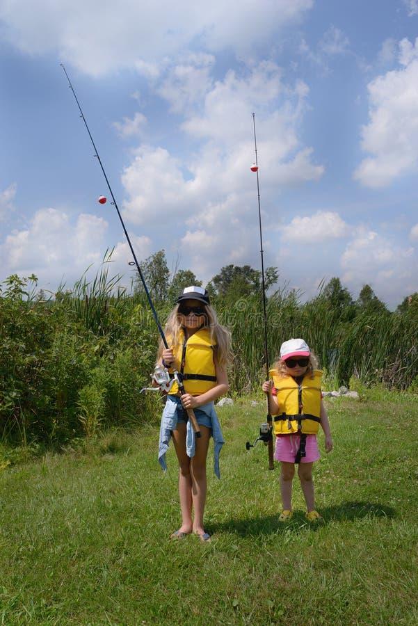 学会钓鱼 两有钓鱼竿的惊人的白肤金发的小女孩准备钓鱼 他们在太阳镜,救生衣佩带 免版税库存照片