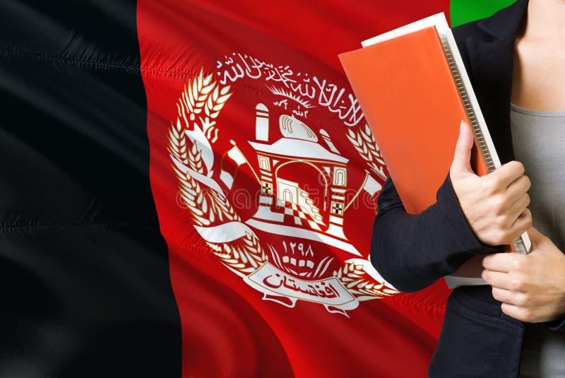 学会阿富汗语言概念 与阿富汗旗子的年轻女人身分在背景中 拿着书,桔子的老师 库存图片