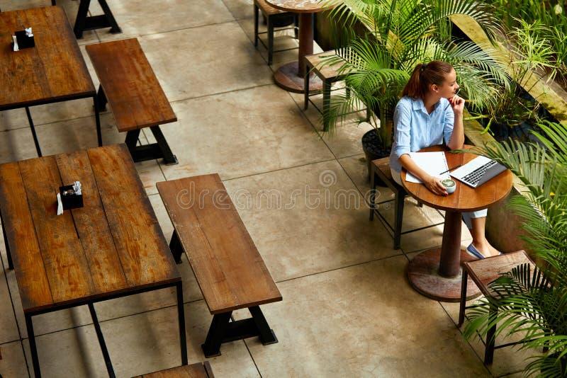 学会,学习 使用便携式计算机的妇女在咖啡馆,运作 免版税图库摄影