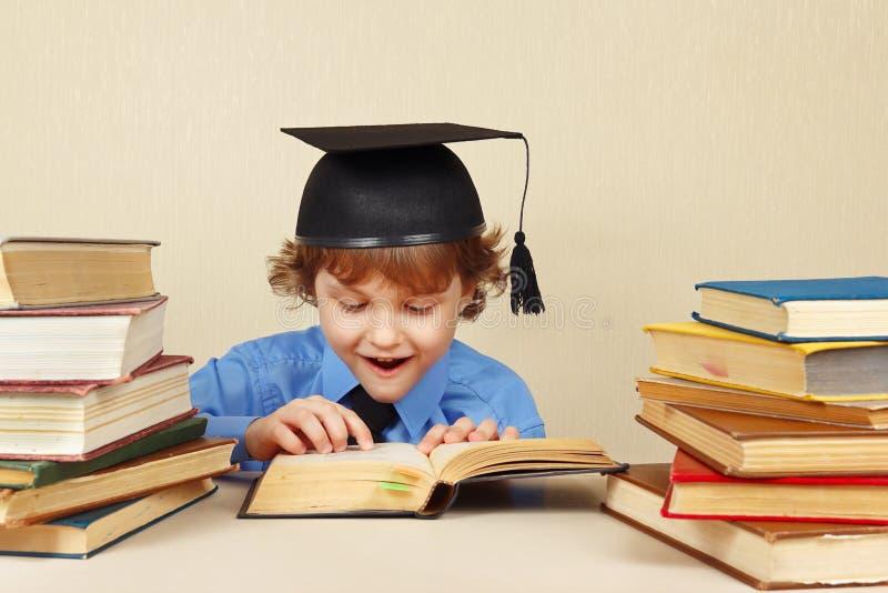 学术帽子的小教授读旧书的 图库摄影