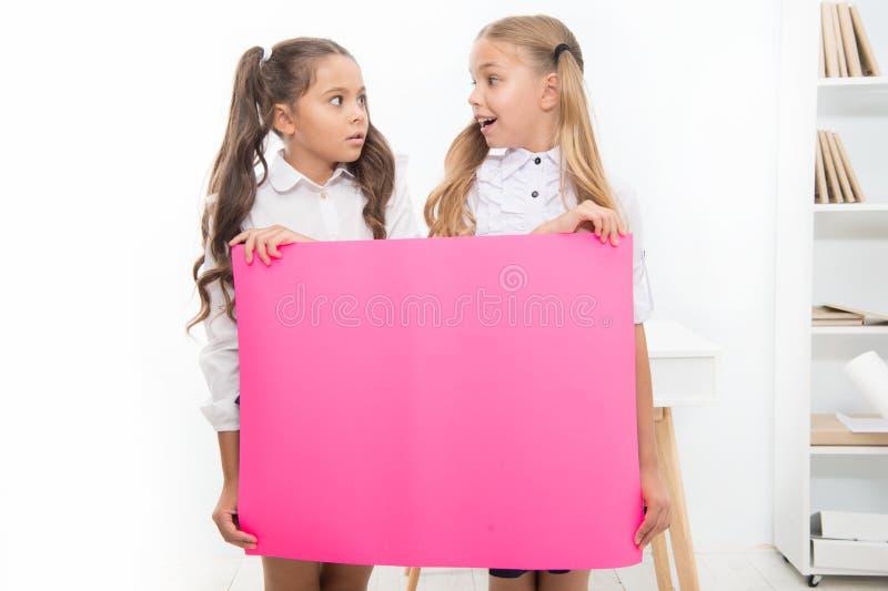 学校公告概念 惊奇的新闻 女孩举行公告横幅 拿着纸横幅为的女孩孩子 库存照片