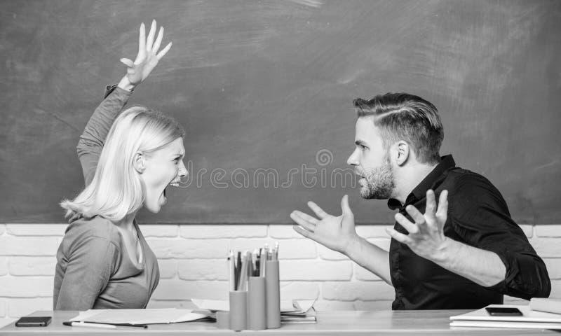 学校冲突 去恼怒的妇女供以人员与她的拳头 老师和男校长是在争吵 争论的夫妇  图库摄影