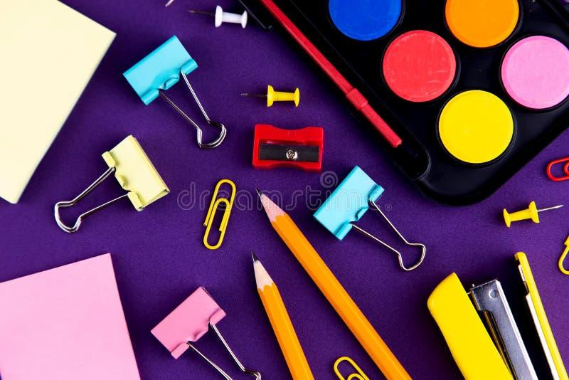 学校办公室供应在一张紫色背景书桌上的文具 r 库存照片