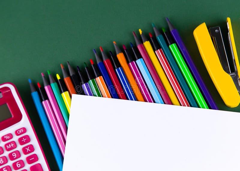 学校办公室把在拷贝空间上的白皮书供给在一张绿色背景书桌上的文具 r 免版税库存图片