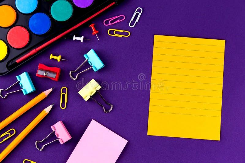 学校办公室把拷贝空间供给在一张紫色背景书桌上的文具 r 库存图片