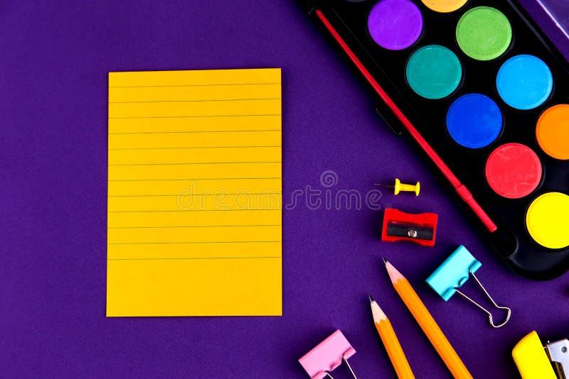 学校办公室把拷贝空间供给在一张紫色背景书桌上的文具 r 免版税库存图片