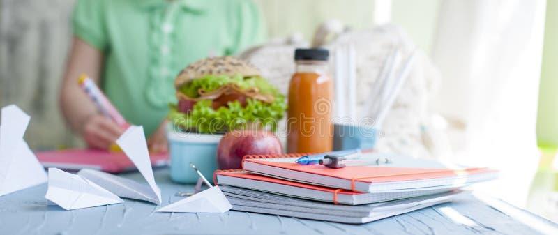 学校午餐和汁液的,健康午餐三明治 在桌和女小学生上的教科书 复制空间 免版税库存图片