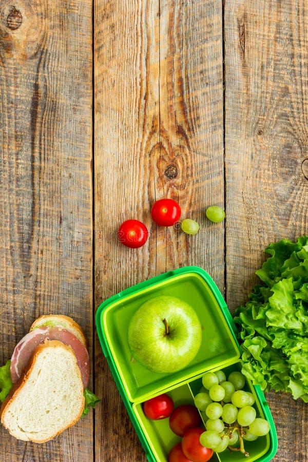 学校午餐在饭盒背景顶视图嘲笑的集合用苹果和菜 库存照片