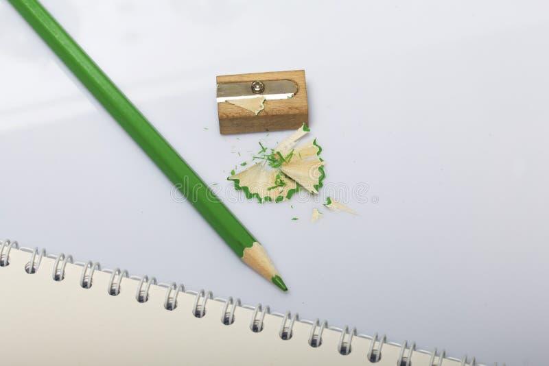 学校和教的文具 笔记薄和绿色铅笔写和画的 有铅笔刮的铅笔刀 库存图片