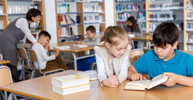 学校图书馆两个学童阅读 免版税库存图片