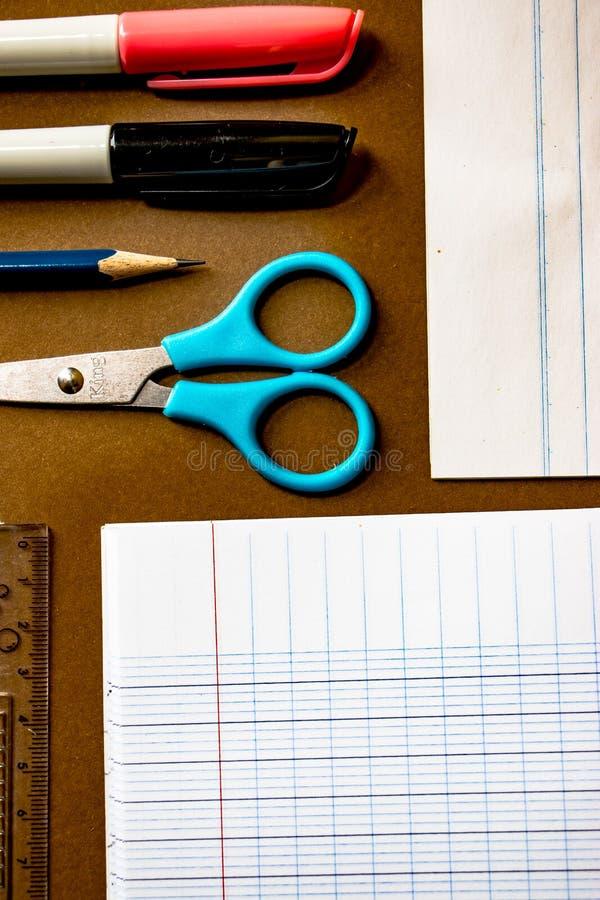 学校在棕色背景的文具辅助部件顶视图照片  库存照片